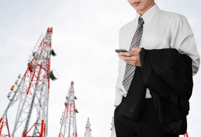 Business employee using smartphone with Telecommunication towers background