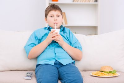 Chubby kid with junk food on the sofa