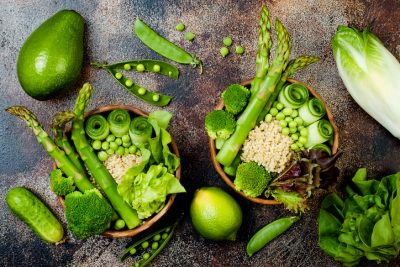 Vegan, detox green Buddha bowl recipe with quinoa, cucumber, broccoli, asparagus and sweet peas. Top view, flat lay, copy space