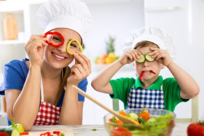 Happy cute family have fun in the kitchen with vegetables