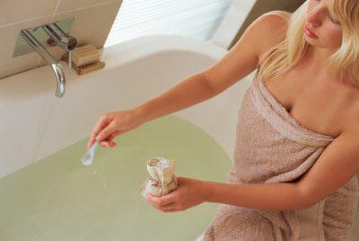 Woman sprinkling salt crystals into bath water