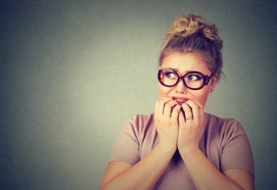 nervous stressed nerdy woman in glasses biting fingernails
